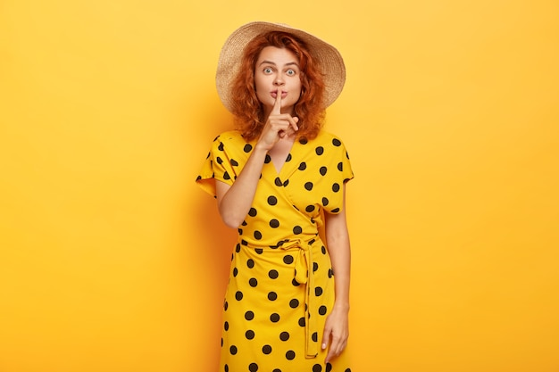 Cute young girl shows shush gesture with surprised expression, keeps index finger over mouth, has ginger wavy hair, dressed in fashionable polka dot dress, tells secret, isolated on yellow  wall