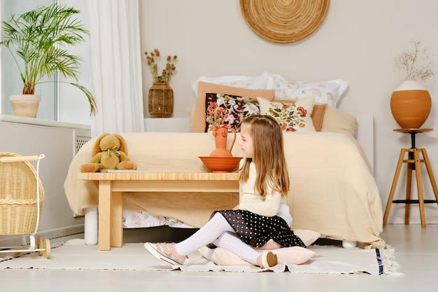 Cute young girl sits on the floor in bedroom and looks to the window