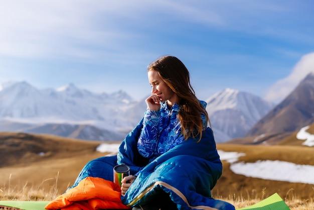 귀여운 어린 소녀는 백인 산의 배경에 앉아 명상하고 자연과 태양을 즐깁니다