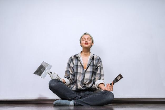 Симпатичная молодая девушка сидит на полу в своей новой квартире, держит кисть и лопатку, ремонт