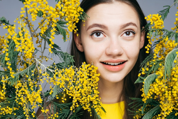 노란 미모사의 큰 꽃다발을 들고 웃고 있는 귀여운 어린 소녀