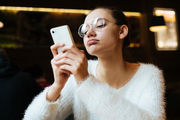 Симпатичная молодая девушка-студентка в белой куртке и очках сидит в кафе и пишет сообщение в телефон