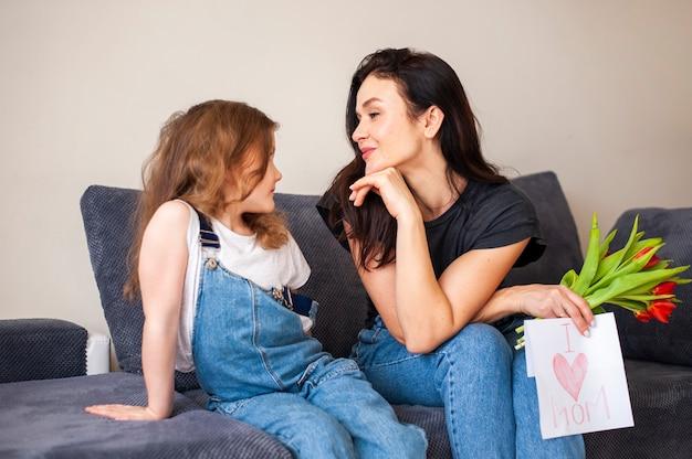 Симпатичная молодая девушка удивляет маму цветами