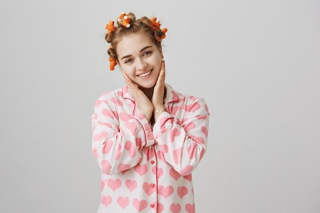 Милая молодая девушка трогает чистую кожу, носит пижаму и бигуди