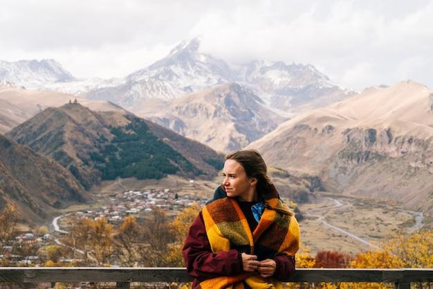 スカーフの肩に乗って、山の自然ときれいな空気を楽しんでいるかわいい若い女の子の旅行者