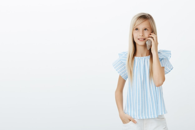 Cute young girl waiting on phone while mom answer. portrait of dreamy happy blond daughter in stylish blue blouse, holding hand in pocket, looking up and talking on smartphone