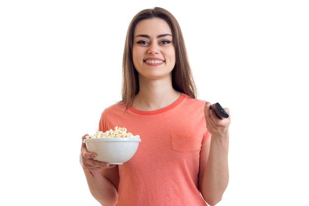 Cute young girl watch a tv and eats a pop-corn isolated on white background