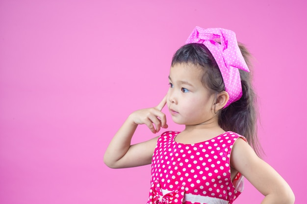 Cute young girl wearing a red striped shirt, tied a pink bow on the head and pink .