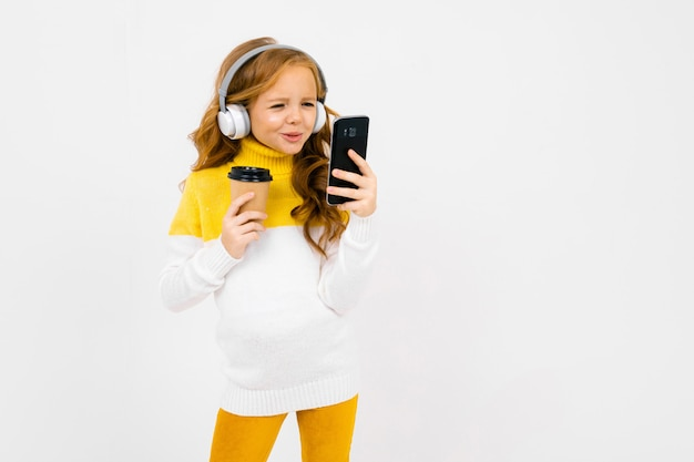 Cute young girl in white headphones looks at the phone and holds a glass