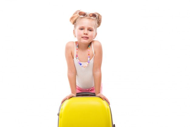 Cute young girl in white shirt, pink shorts and sunglasses stand near yellow suitcase