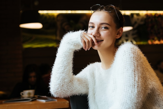Cute young girl in a white sweater sitting in a cafe after work, smiling