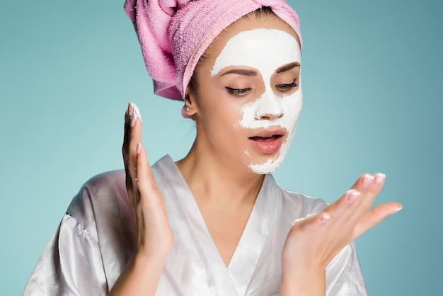 頭にピンクのタオルを顔に白い保湿マスクを適用してかわいい若い女の子
