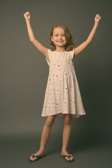 흰색 드레스를 입고 금발 머리를 가진 귀여운 어린 소녀