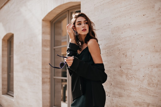 Cute young girl with dark wavy hairstyle and bright makeup, silk dress, black jacket, holding sunglasses in hands and looking away against beige building wall