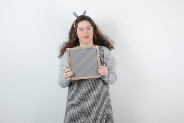 Милая молодая девушка с синдромом дауна держит рамку.