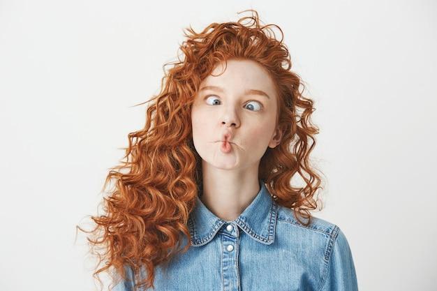 Симпатичная молодая девушка с рыжими вьющимися волосами, делая смешное лицо. копировать пространство