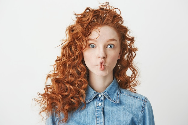 Cute young girl with foxy curly hair making funny face . copy space.