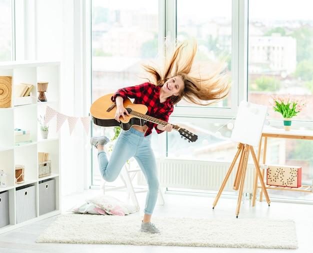 Милая молодая девушка с гитарой в прыжках в высоту дома