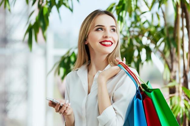 白いブラウスを着て、カラフルな買い物袋を持って立って、携帯電話を持って、ショッピングのコンセプトを明るい茶色の髪と赤い唇を持つかわいい若い女の子。