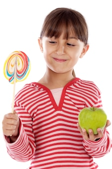 Cute young girl with one lollipop and one apple over white background