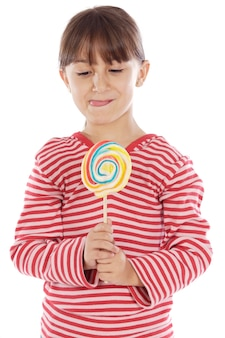 Cute young girl with one lollipop over white background
