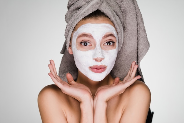 A cute young girl with a towel on her head applied a useful white mask on her face, a spa procedure