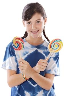 흰색 배경 위에 두 막대 사탕을 가진 귀여운 어린 소녀