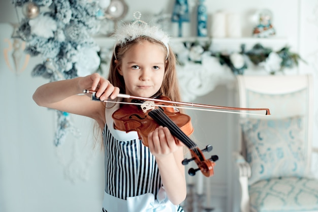 Cute young girl with violin in christmas decoration room.