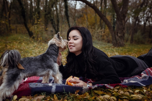 Cute young girl with yorkshire terrier dog in the park in autumn. concept of care and friendship