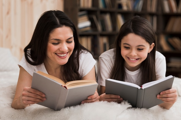 Cute young girl and woman reading books