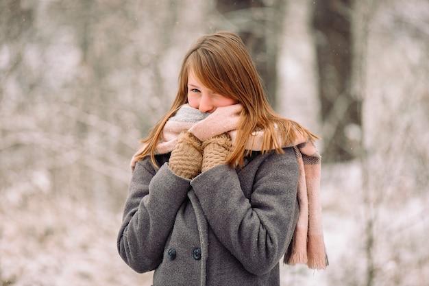 귀여운 어린 소녀 겨울 배경에 귀여운 포즈 스카프에 싸여.