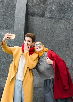 Ragazze sveglie che prendono insieme un selfie