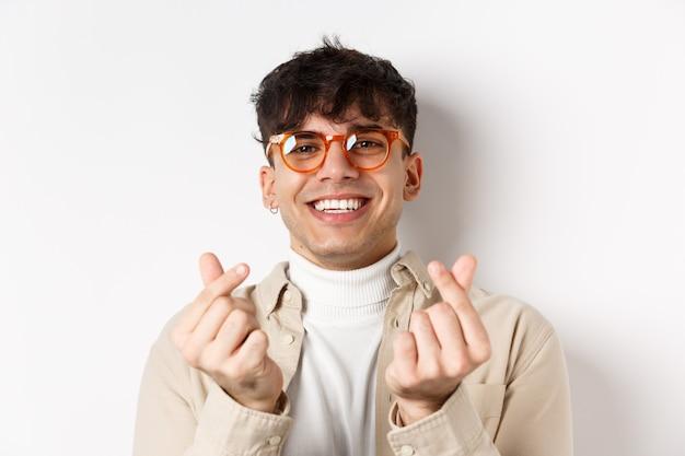 白い背景の上に立って、笑顔と指の心を示すメガネのかわいい若い男