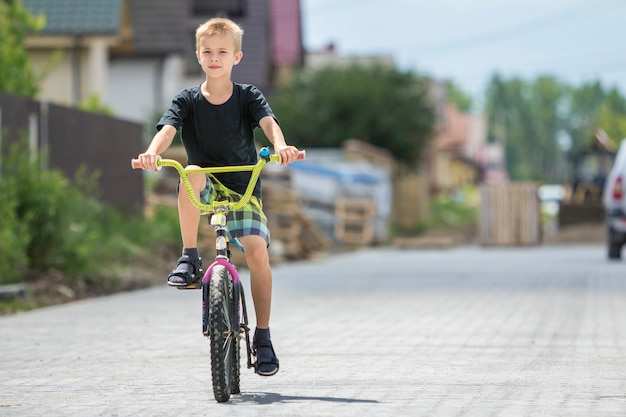 Cute young handsome blond boy in casual summer clothing riding child bicycle along sunny empty paved street