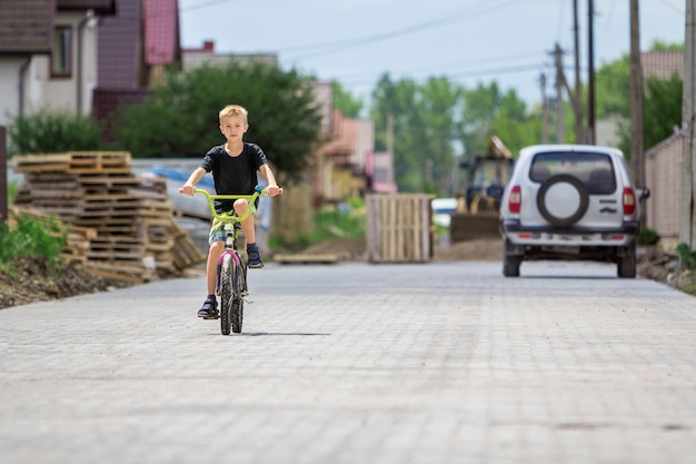 Cute young handsome blond boy in casual summer clothing riding child bicycle