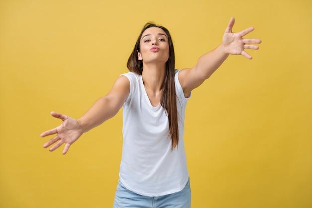 Милая молодая счастливая мечтающая женщина в белой футболке изолирована на желтом фоне, давая воздушный поцелуй