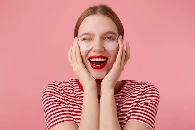 Carina giovane signora dai capelli rossi felice in una maglietta a righe rosse, con le labbra rosse, molto soddisfatta delle nuove toppe, ammiccante e ampiamente sorridente, si tocca il viso con le dita. stand.
