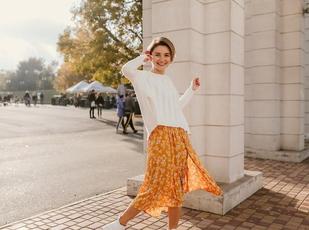 화창한 가을 날 노란색 프린트 드레스와 니트 흰색 스웨터를 입은 귀여운 젊은 행복한 웃는 여자