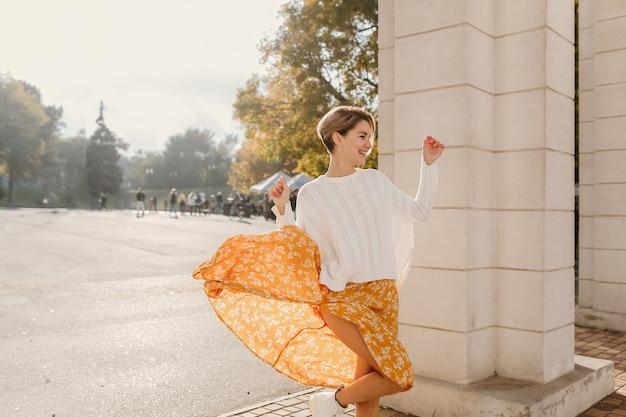 Carina giovane donna sorridente felice in abito stampato giallo e maglione bianco lavorato a maglia nella soleggiata giornata autunnale