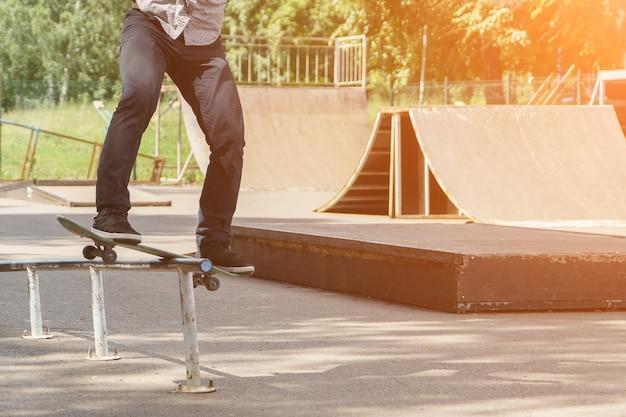 かわいい若い流行に敏感な男は暖かい夏の日、日光のスケートパークでスケートボードでトリックを示しています