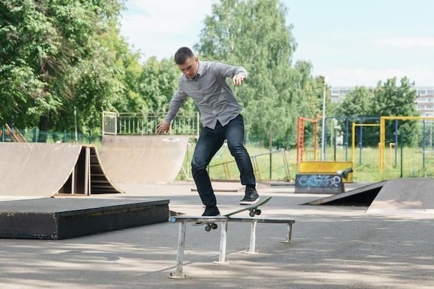 かわいい若い流行に敏感な男は暖かい夏の日にスケートパークでスケートボードでトリックを示しています