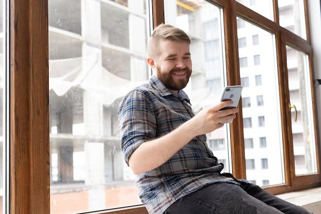 세련된 옷을 입은 귀여운 젊은 힙 스터 남자는 스마트 폰과 큰 창문 근처의 무선 인터넷을 사용하여 소셜 네트워크에 앉아 있습니다. 인터넷 중독.