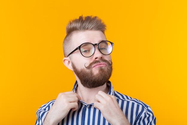 黄色の壁にポーズをとっている間、口ひげと眼鏡のひげを持つかわいい若い流行に敏感な学生の男は彼のシャツをまっすぐにします
