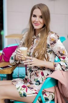 カフェ、春夏のファッショントレンドに座っているかわいい若い流行に敏感なスタイリッシュな女性