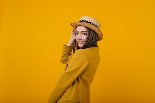 トレンディな明るいジャケットのポーズでかわいい若い女性。楽しんでいる麦わら帽子の女性モデル