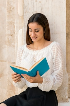 Cute young lady reading book