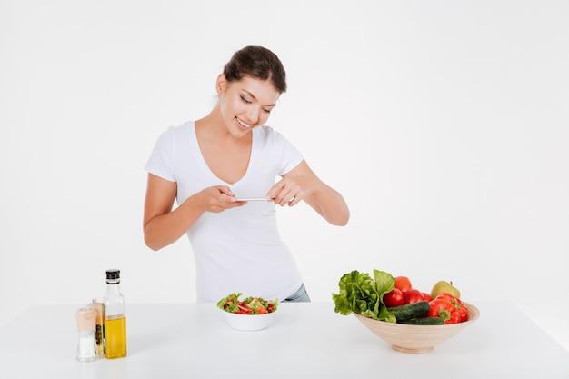 Милая барышня сфотографирует овощной салат на свой телефон