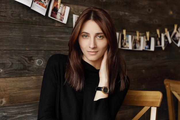 微妙な笑顔でじっと見つめながら、黒い髪を緩め、首に手を当ててかわいい若い女性。自由時間中にコーヒーショップでリラックスできる魅力的な若いヨーロッパの女性