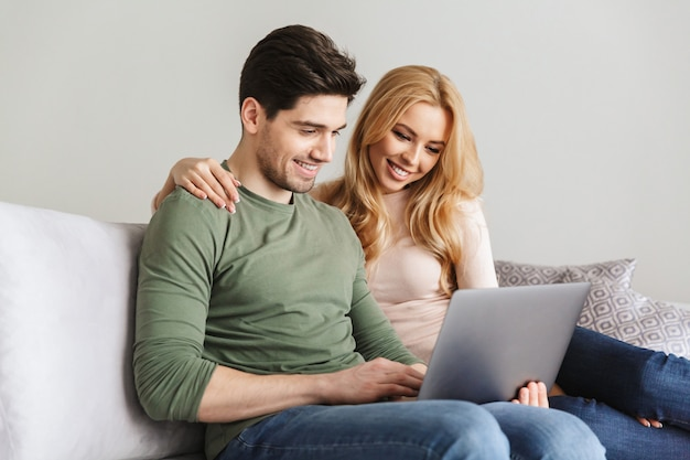 Cute young loving couple sitting on sofa using laptop computer.