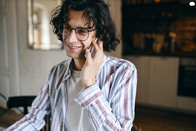 Giovane maschio sveglio in occhiali che parla sul cellulare.
